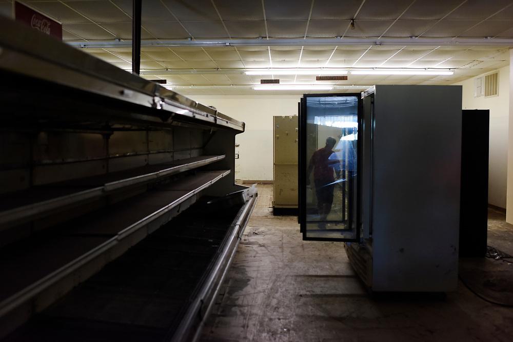 Jim Snoddy is framed by glass doors as he walks the dimply lit aisles of Snoddy's.