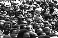 Contrast of race. Small white boy seen in a sea of black African faces whilst they wait to pay their respects at the funeral of President Jomo kenyatta in Nairobi, Kenya in August 1978. Photographed by Terry Fincher