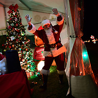 MILTON, DE:  Denny Huss, 70, in his 6th year as Santa, reacts to cars passing by at the Winter Wonderland, an entirely stay-in-your-car experience, drive-thru holiday light attraction in Milton, DE on December 13, 2020. The pandemic has forced difficult decisions about maintaining the holiday tradition of visits to Santa Claus versus safety concerns.  Plexiglass dividers, face shields, and physical distancing are among the precautions for those locations that have proceeded with Santa photo opportunities.  CREDIT:  Mark Makela for The New York Times