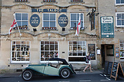 Vintage car outside The Talbot pub and restaurant in Stow on the Wold in The Cotswolds, United Kingdom. Stow-on-the-Wold is a small market town and civil parish in Gloucestershire, England. The town was founded as a planned market place by Norman lords, to take advantage of trade on the converging roads. The Cotswolds is an area in south central England. The area is defined by the bedrock of limestone that is quarried for the golden coloured Cotswold stone. It contains unique features derived from the use of this mineral; the predominantly rural landscape contains stone-built villages and historical towns.