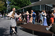 Tango dancing in Spitalfields, London, UK. This crowd of people has gathered in a social dance class and meet up on a sunny Sunday summer day. It's a gathering that feels very fun and positive and warm.