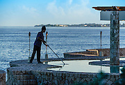 Man cleans resort oceanfront pool, Negril, Jamaica
