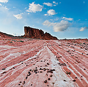 Conglomerate rocks lie on red and white striped sandstone in White Domes area of Valley of Fire State Park, Nevada, USA. Starting more than 150 million years ago, great shifting sand dunes during the age of dinosaurs were compressed, uplifting, faulted, and eroded to form the park's fiery red sandstone formations. The park also boasts fascinating patterns in limestone, shale, and conglomerate rock. The park adjoins Lake Mead National Recreation Area at the Virgin River confluence, at an elevation of 2000 to 2600 feet (610-790 m), 50 miles (80 km) northeast of Las Vegas, USA. Park entry from Interstate 15 passes through the Moapa Indian Reservation.