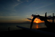 Traditional Balinese outrigger canoes, jukung, silhouetted against rising sun. Sanur Beach, Bali, Indonesia.