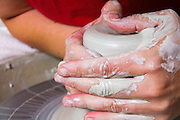 An European female potter in her workshop shapes clay on a potter's wheel. Closeup of her hands