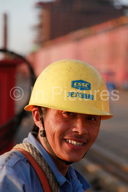 A worker looks up after finishing his shift at the China State Shipbuilding Corp.'s (CSSC) Longxue Shipyard in Guangzhou, Guangdong Province, China, on Sunday, Nov. 13, 2011. China is the world's biggest shipbuilder, however recent economic downturns have caused a glut in supplies.