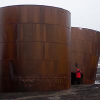 A tourist photographs tanks at Whaler's Bay, Deception Island, Antarctica.