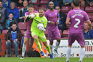 Rochdale defender Jim McNulty (4) holds onto Scunthorpe United goalkeeper Jak Alnwick (25)  during the EFL Sky Bet League 1 match between Scunthorpe United and Rochdale at Glanford Park, Scunthorpe, England on 8 September 2018. Photo Ian Lyall