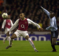 Photo: Greig Cowie<br />Champions League Second Group Stage. Group B Arsenal v Ajax. 18/02/2002<br />Thierry Henry challenges for the ball with Ajax's Hatem Trabelsi