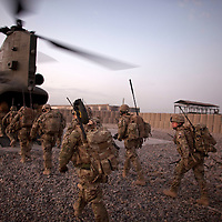 British soldiers from 1PWRR (Princess of Wales Regiment) board a CH-47 Chinook helicopter in preperation for an air assault into a contested region of Helamnd Province. The men are involved in an ongoing series of Operations called Tora Pishaw aimed at disrupting insurgent activity in their AO (Area of Operations). During the most recent 4 day operation the soldiers regularly came under fire from insurgents using small arms, belt fed machine guns and UGL's (Under Slung Grenade Launchers). The soldiers retuned fire using shallow trenches on the edges of ploughed fields or irrigation ditches as cover. Nad I Ali North, Helmand Province, Afghanistan on the 13th of November 2011.
