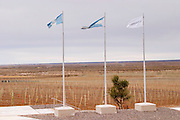 View over the vineyard with Argentinean and family flags on three flag poles. Bodega Familia Schroeder Winery, also called Saurus, Neuquen, Patagonia, Argentina, South America
