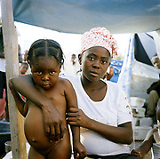 Makidila Appallon, twenty-two, with her daughter ,  Jaunisse Dorlus, aged three, Camp, Puit-Blain.Makidila was in the house when the earthquake struck, but fortunately managed to save the children. Conditions in the camp are hard though and the children are suffering from malnutrition. Jaunisse's swollen stomach is caused by a combination of no food and parasites in the gut.