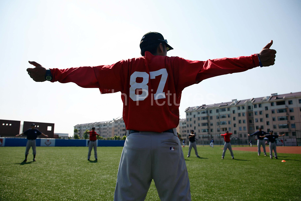 Players and coaches perform warm up drills before an exhibition game at a summer training camp run by Major League Baseball Wuxi, China, on 19 August, 2010.  Targeting teenagers between the ade of 12-15, the league hopes to use the camp to groom potential baseball talent in China and in the long term increase the popularity of the sport in the world's most populous country.