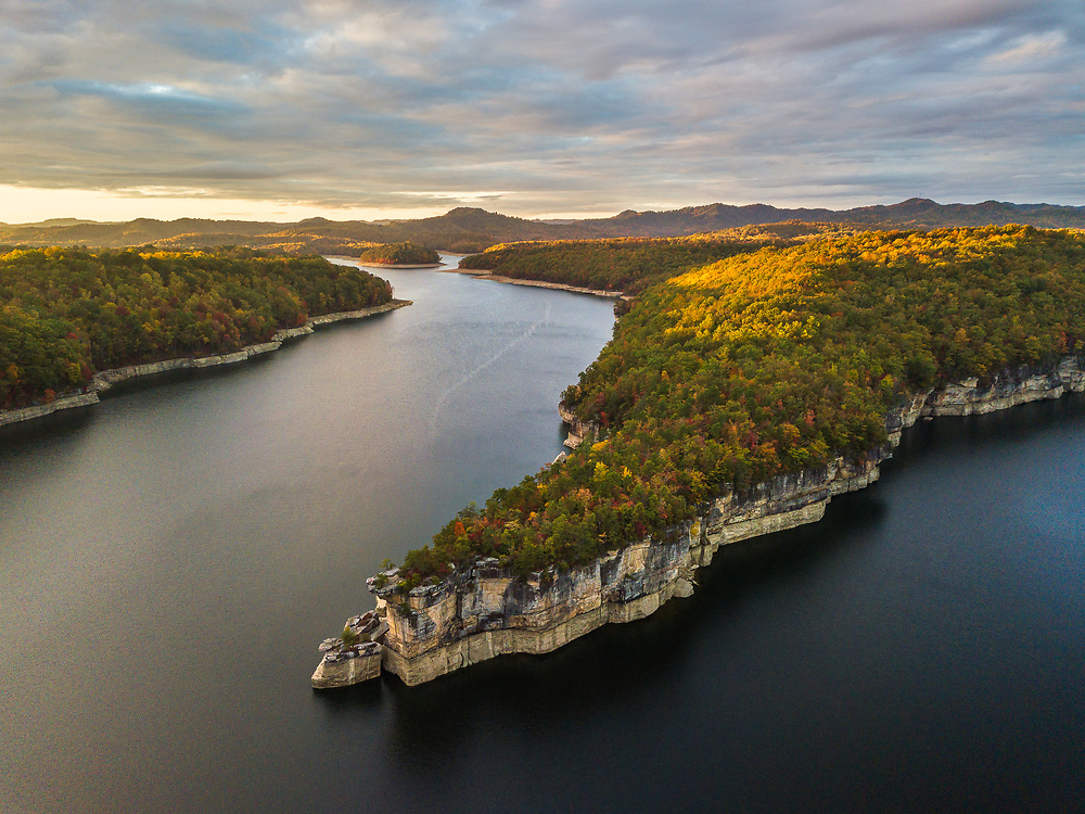The late evening sunlight grazes the tops of the hills above the clifflines of Summersville Lake in early Autumn.