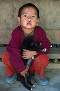 Nyshi child & puppy<br /> Nyshi Tribe<br /> Arunachal Pradesh<br /> North East India