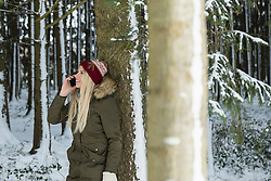 Teenage girl talking on mobile phone in forest, Bavaria, Germany