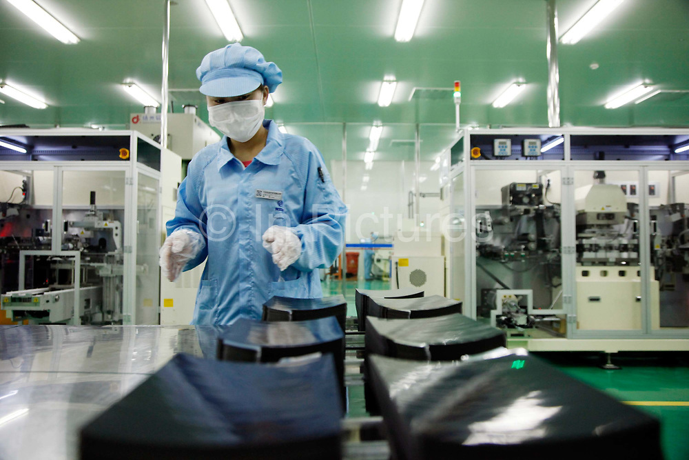 Workers operate on the vehicle battery assembly area of Wanxiang Group's electric automobile division in Hangzhou, Zhejiang Province, China on 25 March, 2011. Wanxiang is China's largest provider of technology for electric cars.