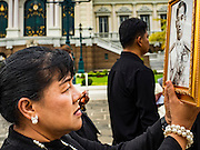 29 OCTOBER 2016 - BANGKOK, THAILAND:  A woman carries a portrait of the late Bhumibol Adulyadej, the King of Thailand, while she walks through the grounds of the Grand Palace Saturday, the first day Thais could pay homage to the funeral urn of the late Bhumibol Adulyadej, King of Thailand, at Dusit Maha Prasart Throne Hall in the Grand Palace. The Palace said 10,000 people per day would be issued free tickerts to enter the Throne Hall but by late Saturday morning more than 100,000 people were in line and the palace scrapped plans to require mourners to get the free tickets. Traditionally, Thai Kings lay in state in their urns, but King Bhumibol Adulyadej is breaking with tradition. His urn reportedly contains some of his hair, but the King is in a coffin,  not in the urn. The laying in state will continue until at least January 2017 but may be extended.      PHOTO BY JACK KURTZ