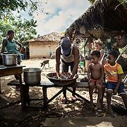 A family on the island of Marajò transforms manually Açai berry pulp.
