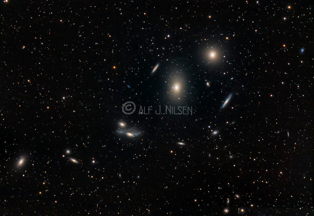 Markarian's Chain, a chain of galaxies forming part of the Virgo Cluster.  The brightest galaxies are the elliptical M84 and M87. Do also see image #73225-Da for the inverted version.
