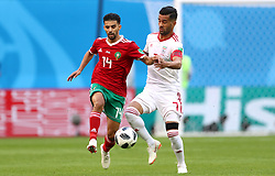 Morocco's Mbark Boussoufa (left) and Iran's Masoud Shojaei battle for the ball
