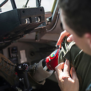 U.S. Air Force Captain Ryan McGuire, C-17 Globemaster III pilot with the 535th Airlift Squadron, adjusts his prosthetic before a training flight, Sep 12, 2017 on Joint Base Pearl Harbor-Hickam. McGuire brought his prosthetist into a C-17 simulator, to make sure his prosthetic can properly push the rudder pedals. U.S. Air Force photo by Staff Sgt. Perry Aston)