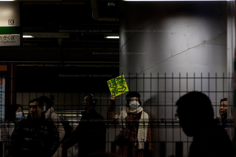 """A Japanese woamn holds a sign saying """"Let's go to vote"""" on the platform of Ogikubo Station as politicians campaign nearby. Ogikubo, Tokyo, Japan. Friday December 14th 2012"""
