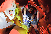 """02 OCTOBER 2009 -- BANGKOK, THAILAND: Volunteers from the Poh Teck Tung Foundation try to help a man who was involved in a motorcycle accident. The man died at the scene. The 1,000 plus volunteers of the Poh Teck Tung Foundation are really Bangkok's first responders. Famous because they pick up the dead bodies after murders, traffic accidents, suicides and other unplanned, often violent deaths, they really do much more. Their medics respond to medical emergencies, from minor bumps and scrapes to major trauma. Their technicians respond to building collapses and traffic accidents with heavy equipment and the """"Jaws of Life"""" and their divers respond to accidents in the rivers and khlongs of Bangkok. The organization was founded by Chinese immigrants in Bangkok in 1909. Their efforts include a hospital, college tuition for the poor and tsunami relief.   PHOTO BY JACK KURTZ"""