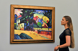 """© Licensed to London News Pictures. 15/06/2017. London, UK. A staff member views """"Murnau - Landschaft mit grünem Haus"""", 1909, by Wassily Kandinsky (estimate GBP15-25m).  Preview of Impressionist and Modern art sale, which will take place at Sotheby's New Bond Street on 21 June.  Photo credit : Stephen Chung/LNP"""