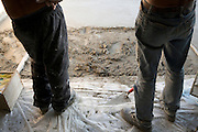 workers taking a break while spreading cement to make a floor