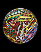 colorful paperclips in round container on a black background