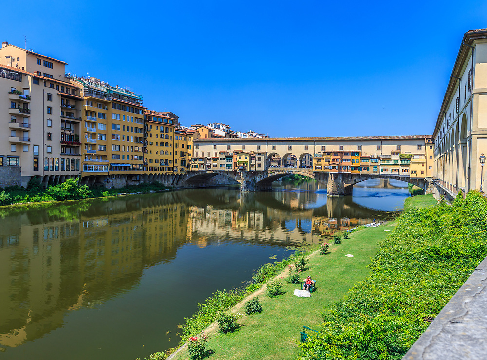 Ponte Vecchio in Florence, Italy. Ponte Vecchio that crosses the Arno river, was built after a flood in 1345. The feature that catches one's eyes is the two-story structure. The Medicis built a second store corridor (Vasari) to avoid contact with the people they ruled.
