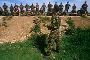 A British Army Gurkha soldier instructs his men during an exercise on Salisbury Plain, the army's infantry training ground. Standing below his men who have lined up on an artificial bank in this military facility in the Wiltshire countryside. Here, the army trains men for urban warfare and a fake village, complete with streets and houses accommodate the soldiers during practice fire-fights. The men here are listening to a brief from a senior officer, hearing the nature of the next exercise and listening intently to his instructions. The officer belongs to the Gurkha Regiment, an elite force of men recruited from the foothills, plains and cities of Nepal and have served within the British army since 1857.
