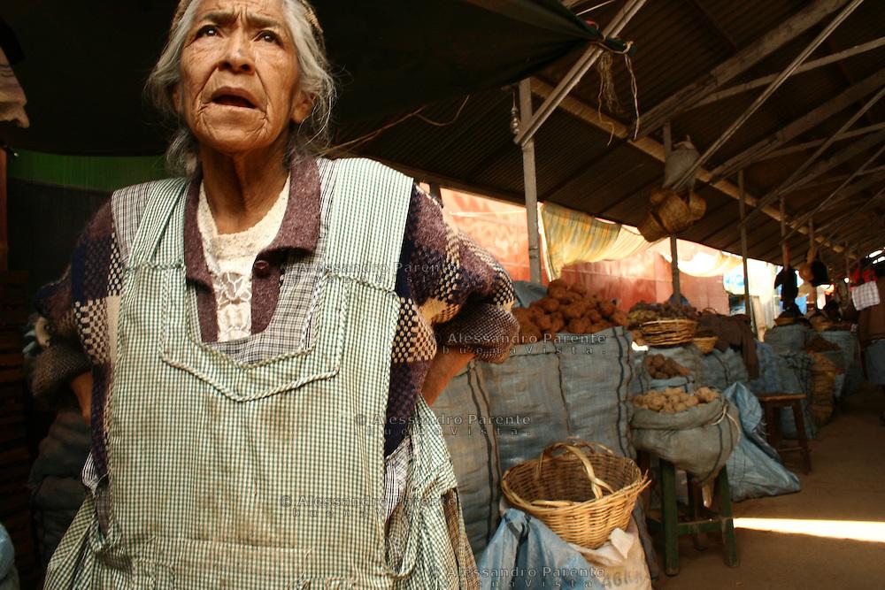 Old woman selling potatoes on a Bolivian market, Cochabamba.