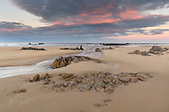 Sunset and red sky on a sandy beach with rocks, Cantabria, Spain<br /> <br /> Sonnenuntergang und Abendrot an einem Sandstrand mit Felsen, Cantabria, Spain