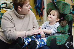 Helper with child with physical and learning disabilities exercising,
