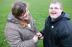Two teenaged friends; one with Downs Syndrome; talking together,