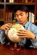 Age 24 Korean businessman studying world geography.  St Paul Minnesota USA