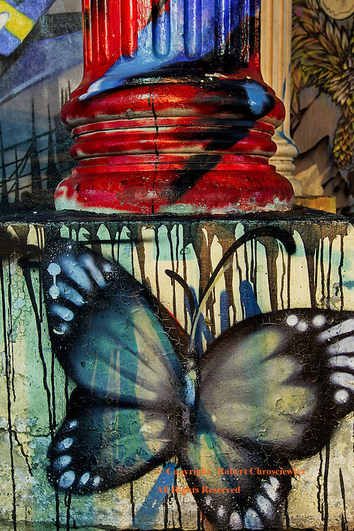 Graffiti Butterfly: Night time view of a large butterfly and other colourful graffiti, that adorns a concrete column, near to Loha Prasat Wat Ratchanatdaram, Bangkok Thailand.