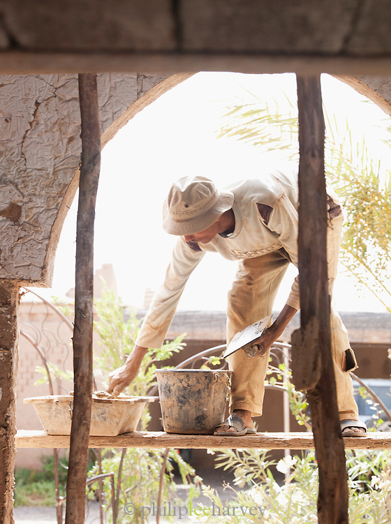 A carpenter renders a wall at a building in the Skoura Oasis in Morocco