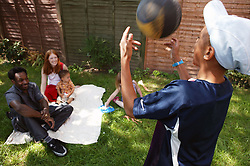 Multiracial family group sitting and playing in the garden,
