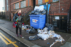 "© Licensed to London News Pictures. 20/12/2020. London, UK. A woman wearing a face covering walks past a pile of rubbish and food waste in Edmonton, north London as restaurants are providing take away service only. Prime Minister Boris Johnson announced on Saturday 19 December, that London and South East of England will move into Tier four restrictions. Under the new restrictions, non-essential shops, hairdressers and leisure and entertainment venues are closed, and a ""stay at home"" message introduced. Photo credit: Dinendra Haria/LNP"