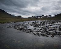 River flows through rugged mountain landscape, near Tjäktja hut, Kungsleden trail, Lapland, Sweden