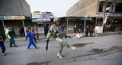 Sgt. Major George Crisostomo kicks a soccer ball while patrolling with other members of the 1st Infantry, 17th Regiment, Mosul, Iraq, Dec. 16, 2005. This is part of an effort to provide security in preparation for Iraq's first post-Saddam parliamentary elections. The western sector is home to Mosul's primarily Sunni population, which has been resistant to the American presence in Iraq.