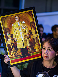 October 13, 2017 - Bangkok, Thailand - A woman holds up a portrait of Bhumibol Adulyadej, the Late King of Thailand, during a mass merit making with 199 Buddhist monks from 14 different temples at Siriraj Hospital in Bangkok. The  revered king died on October 13, 2016 after a prolonged hospitalization. He has lain in state for the last year. The King's four day funeral ceremony will be October 25 - 29, and he will be cremated on October 26. (Credit Image: © Sean Edison via ZUMA Wire)