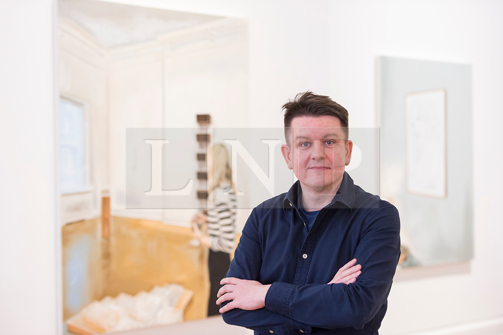 """© Licensed to London News Pictures. 28/11/2019. LONDON, UK. Polish artist Marcin Maciejowski poses with his works (L) """"It Is Enough I'm Delighted, Don't Make Me Understand It"""", and (R) """"Private View (Warhol)"""" both 2019.  First look of """"Private View"""" by Marcin Maciejowski at Galerie Thaddeus Ropac in Mayfair.  The artist's first London exhibition features new large-scale paintings and graphic works on paper merging comic-book and Old Master traditions.  The show runs 28 November to 25 January 2020. Photo credit: Stephen Chung/LNP"""