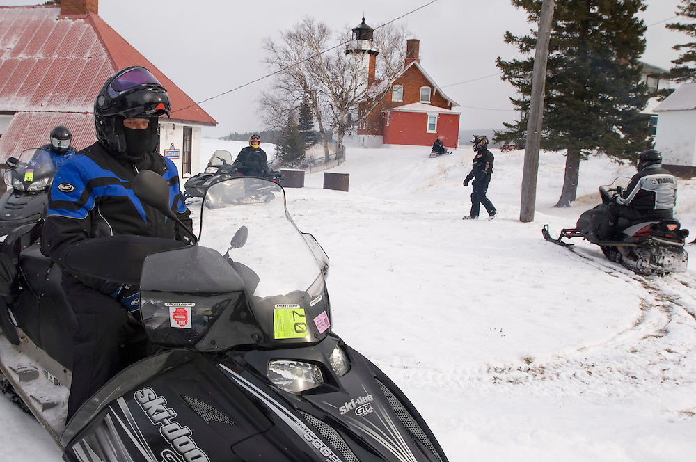 Snowmobilers on a tour of Michigan's Upper Peninsula stop at the Eagle Harbor Lighthouse on Michigan's Keweenaw Peninsula.