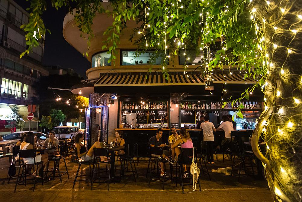 People are seen hanging out at Dailyz Bar in Tel Aviv's Merkaz Hair neighborhood