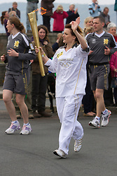 © Licensed to London News Pictures. 19/05/2012. Penzance, UK. A Torchbearer carries the Olympic Flame through Penzance as part of its 8,000 mile journey across the UK. . Photo credit : Ashley Hugo/LNP