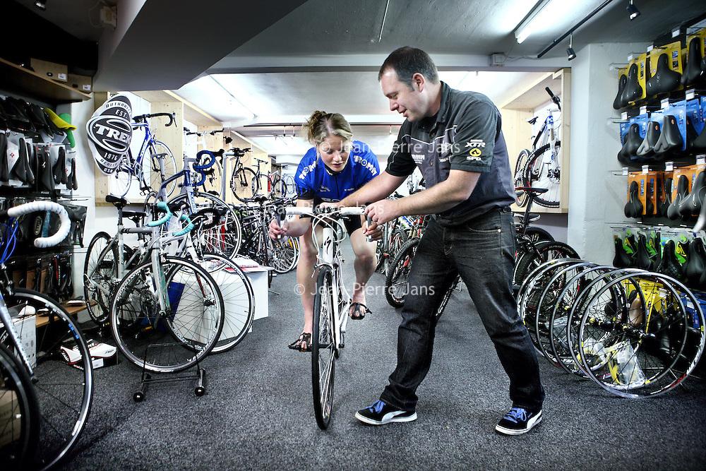 Nederland, Amsterdam , 23 juli 2011..Edgar Tromm van fietshandel Tromm op Olympiaplein geeft een vrouwelijke klant uitleg omtrent een wielrennersfiets..Tegenwoordig schijnen steeds meer vrouwen geinteresseerd te zijn in de wielersport...Foto:Jean-Pierre Jans